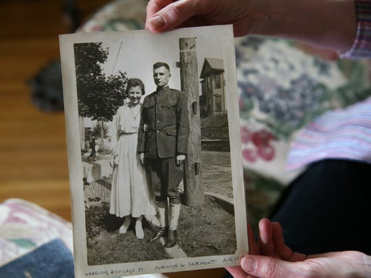Sue Ellen Windsor looks over a diary and photo albums kept by her grandfather, J. Earl Windsor, during his time in Rochester during WWI when he was a student at the Aerial Photography School at Eastman Kodak, Tuesday, May 23, 2017, at her Penfield home. Here she holds up a photo of her grandparents, J. Earl Windsor and Letha Windsor, taken in 1918.