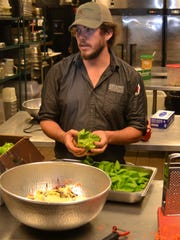 Jack Doggett, kitchen manager at Spirits Food & Friends, prepares a dish using butter lettuce from Gray-Walk Farms.