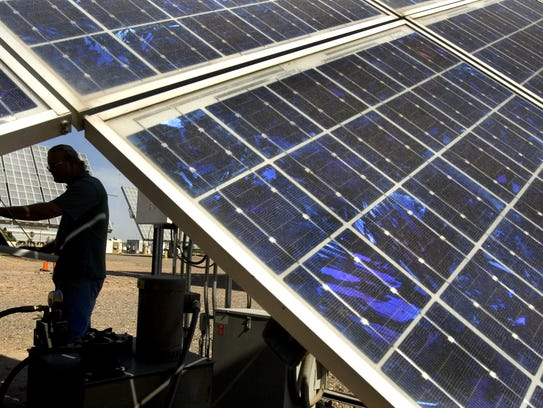 A solar technician installs new tracking software on