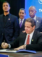 New York Gov. Andrew Cuomo, surrounded by state and
