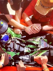 Chaplain Mike Griffith says a prayer with racer Tyler