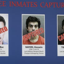 Three inmates captured are seen on a video monitor at Orange County Sheriff's news conference in Santa Ana, Calif., Monday, Feb. 1, 2016. The inmates from left, Bac Duong, 43, Hossein Nayeri, 37, and Jonathan Tieu, 20, who escaped on Jan. 22 from Central Men's Jail in Orange County. Duong turned himself in Friday and the other two were arrested in San Francisco on Saturday.