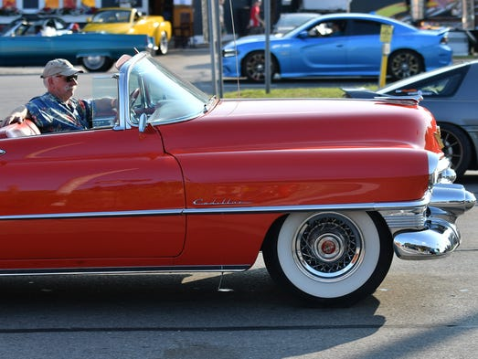 The relaxed driver of a red Cadillac cruises up Woodward