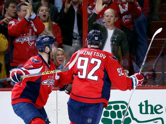 Washington Capitals defenseman Karl Alzner (27) and center Evgeny Kuznetsov (92), from Russia, celebrate Kuznetsov's goal during the first period of Game 5 in the first round of the NHL hockey Stanley Cup playoffs against the New York Islanders, Thursday, April 23, 2015, in Washington. (AP Photo/Alex Brandon)