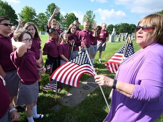 Peg Rizzuto, right, principal of St. Rose of Lima Elementary School, asks students questions about Memorial Day before the school places flags at Holy Savior Cemetery