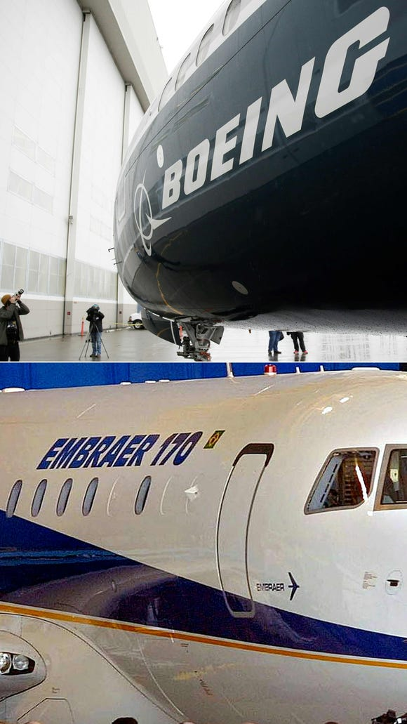 This combination of file pictures created on July 05, 2018 shows the first Boeing 737 MAX 9 airplane (top) at the Boeing factory in Renton, Washington, on March 7, 2017; and Embraer's new passenger jet, the ERJ 170 during a ceremony at the company's manufacturing plant in Sao Jose de los Campos, Brazil on Oct. 29, 2001.