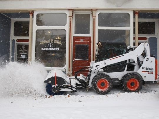 A Bobcat used a rotating brush to clear the sidewalks on Main Street, LeRoy, this week.