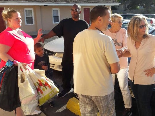 Dawn Swain (far left), Corey Swain Jr. (second from right) and Corey Swain Sr. (center, black shirt) receive donated goods from Betty Santoro (second from right) and others.