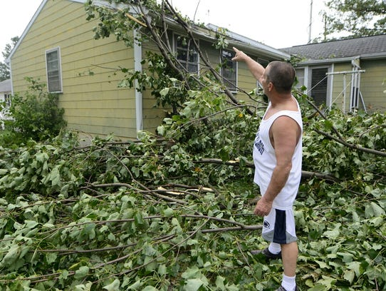 Gordon Ziegler points to damage on his home in the