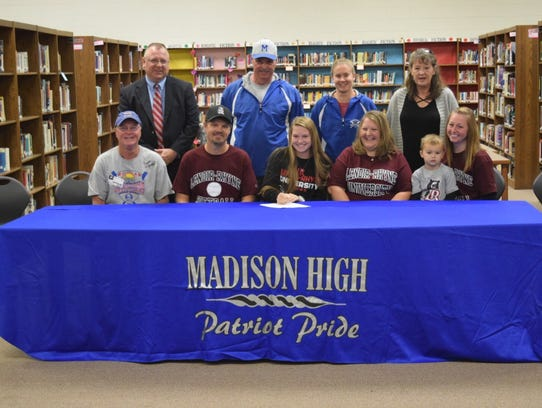 Madison High School senior Hannah Jennings signs to play softball with Lenoir-Rhyne University joined by (back row, left to right) Madison High School Principal Wesley Floyd, head softball coach Andy Gregg, assistant coach Rebecca Huff, grandmother Joan Shepherd and (bottom row) step-grandfather Jerry Shepherd, father Denver Jennings, mother Tammy Jennings, aunt and cousin Tracey and Jase Peterson.