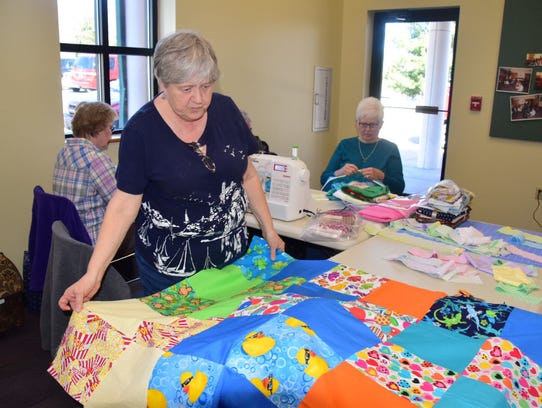 """Sherry Scott examines the top of her """"I Spy"""" quilt."""