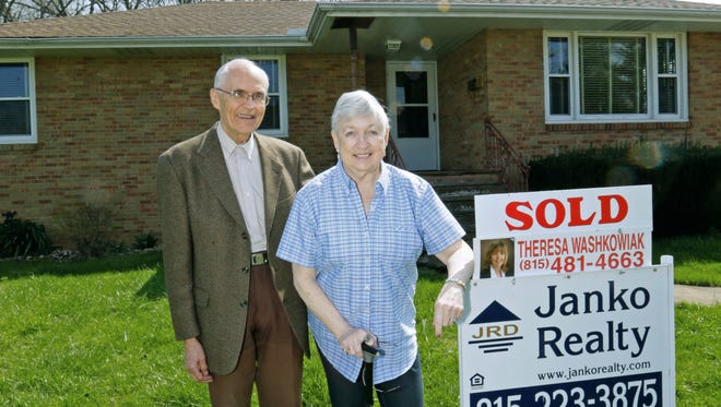 In this April 13, 2017  photo, Jack and Sandy Daniels pose for a picture outside their new home in Oglesby, Ill. The Daniels' never intended to move when they built their home in Rockton, Ill., more than 40 years ago. But as the grew older they decided it was time to downsize.