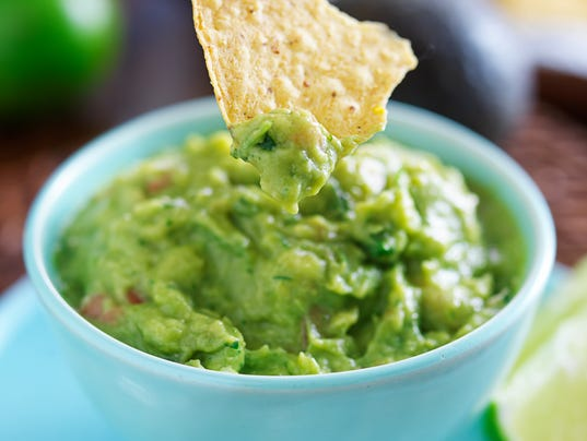 dipping tortilla chip in mexican guacamole