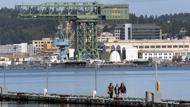 PSNS looms in the background as a trio of pedestrians wander along the Port Orchard Marina dock.