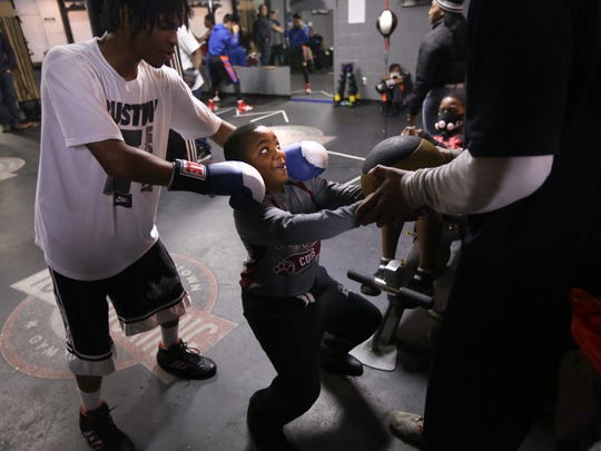 Christopher Roberts, 9, of Detroit is shown an exercise with a medicine ball by fellow student Cortez Todd, 17, of Detroit at the Downtown Youth Boxing Gym in Detroit on Dec. 16, 2014.