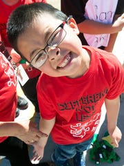 "While students at Central Elementary School practice for Project UNIFY, an Autism Awareness Team Building Competition, Eric Lin, 6, looks up at the camera wearing a shirt that reads, ""Different Not Less."""