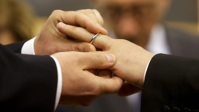 """In this May 21, 2015 file photo, Mauro Cioffari, left, puts a wedding ring on his partner Davide Conti's finger as their civil union is being registered by a municipality officer during a ceremony in Rome's Campidoglio Capitol Hill. Pope Francis endorsed same-sex civil unions for the first time as pope while being interviewed for the feature-length documentary """"Francesco"""" which premiered Wednesday, Oct. 21 at the Rome Film Festival."""