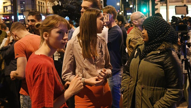 Onlookers gather near a police line at Finsbury Park after a van collision incident in north London on June 19, 2017.