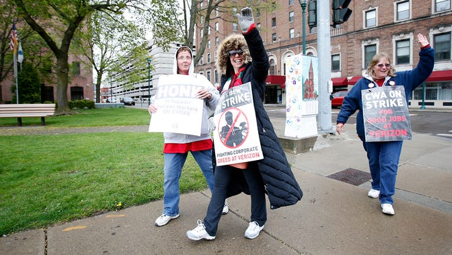 Verizon unionized workers, from left, Andrea Frank, Joann Baldwin and Kelly Carey, all of Elmira, wave at a motorist honking a horn Friday while they protest Verizon corporate practices in Wisner Park.