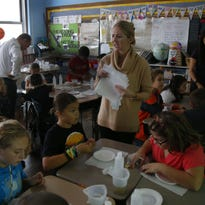 Jill Puffenbarger helps students in her fourth-grade class at Highlands Elementary School with science experiments.