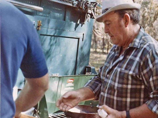 "Floyd ""Fingers"" O'Bannon cooks for Ogden Phipps during a camping trip in 1970."
