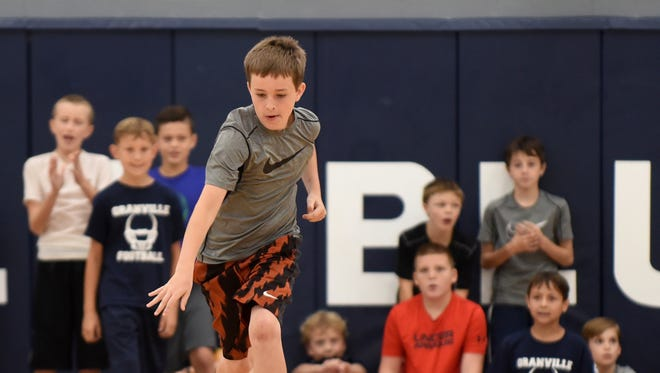 Zach Windley's teammates cheer him on as he takes off from the baseline during a dribbling relay race on the final day of youth basketball camp at Granville High School on Thursday, June 29, 2017.