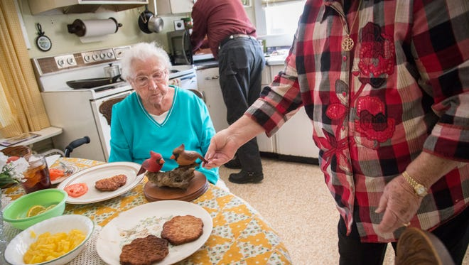 Caregiver Lynda Stamey sets the table for Mozelle Smith, left, while neighbor Randy Martin heats up a side dish for her.