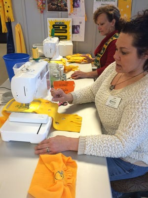 Project leader Kari Watt, front, and volunteer Trish Wesley embroider cheesy scarves on sewing machines in the dining room at New Community Shelter in Green Bay. A few thousand scarves made by shelter residents and staff as well as community volunteers have been sold since the start of the Packers season to raise money for shelter operations.