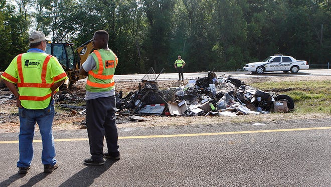 Investigators oversee the cleanup of a deadly crash on Interstate 55 near the DeSoto/Tate County line south of Hernando, Miss., Thursday, Aug. 20, 2015. Two people were killed in the fiery accident that tied up rush hour traffic, The Commercial Appeal reported.