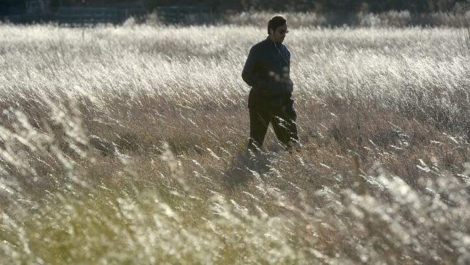 Sultan Alotaibi, a CSU mechanical engineering major, from Kuwait, walks through the tall grass in Ross Natural Area Tuesday Nov. 25, 2014.