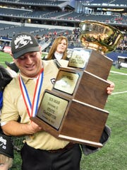 Crowell coach Nathan Hayes smiles as he holds the coaches' trophy celebrating the Wildcats' 78-52 championship win at the UIL football Six-Man Division I state championship game at AT&T Stadium in Arlington Saturday afternoon.