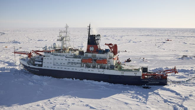 The Polarstern research vessel is shown in the Arctic ice, with research stations in the background.