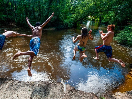 Teenagers leap into Autauga Creek at Doster Well Park in Prattville on Friday afternoon June 16, 2017.