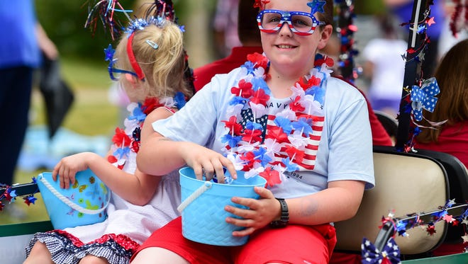A parade rider throws candy on Monday, July 4, 2016, during the Windsor Heights Independence Day Parade.