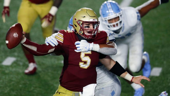 North Carolina linebacker Jeremiah Gemmel, behind, tries to take down Boston College quarterback Phil Jurkovec (5) during the second half of an NCAA college football game, Saturday, Oct. 3, 2020, in Boston.