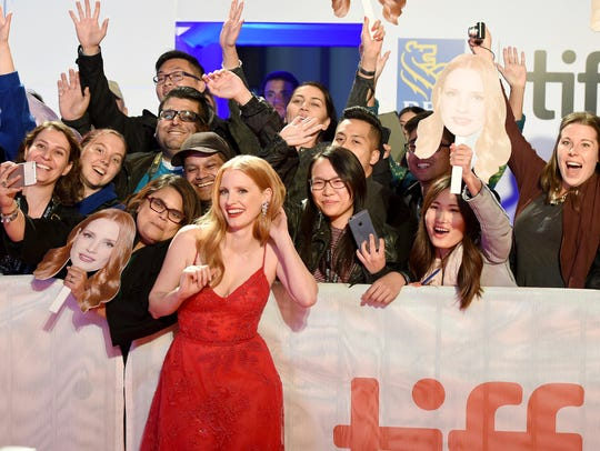 Jessica Chastain poses with fans as she attends the
