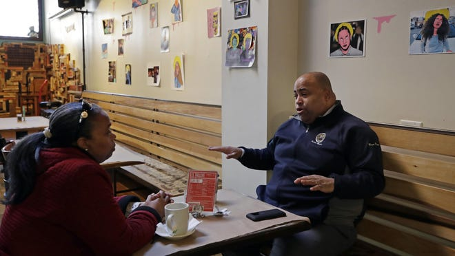 """In this Feb. 6, 2019 photo, Mayor Dan Rivera, right, chats with Pastor Milagro Grullon at El Taller Cafe in Lawrence, Mass. Democratic U.S. Sen. Elizabeth Warren's """"big announcement"""" about her 2020 plans will be made in this blue-collar, heavily immigrant former mill town that reflects the economic themes she's been hitting."""