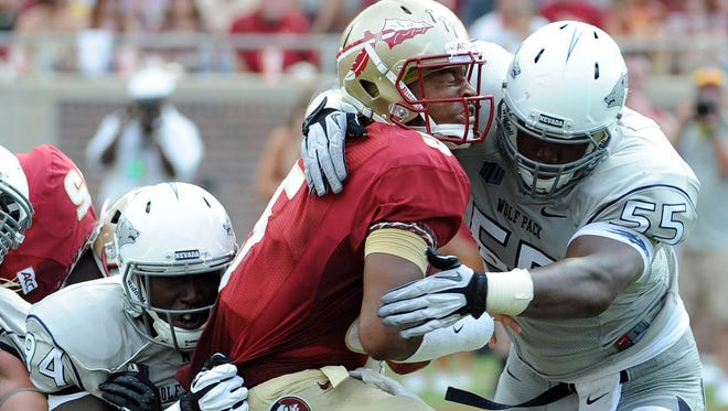 Nevada defenders Lenny Jones, left, and Rykeem Yates take down Florida State quarterback Jameis Winston during a game in 2013.