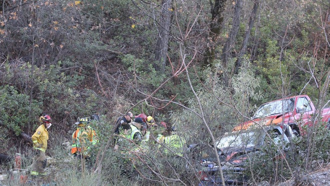Emergency personnel work to free a woman trapped in her car following a two-vehicle traffic accident Thursday on Highway 299 east of Whiskeytown Lake.