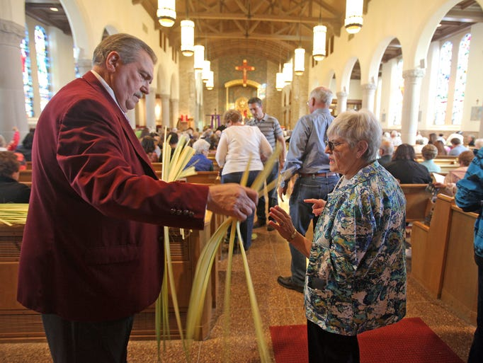 Usher Vincent Rizzo, left hands out Palms to parishioners during Palm Sunday vigil Mass at St. Gregory the Great Church in Harrison on April 12, 2014.  On Palm Sunday, Christians commemorate Jesus' entry into Jerusalem when palm branches were strewn before him.