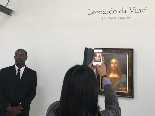 A visitor to Christie's San Francisco display of Leonardo da Vinci's Salvator Mundi painting takes a photo of the work, which goes on sale in New York Nov. 15 and is expected to fetch well north of $100 million.