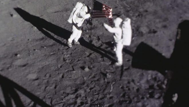 Neil Armstrong and Buzz Aldrin plant an American flag on the moon (photo captured by 16mm Data Acquisition Camera).