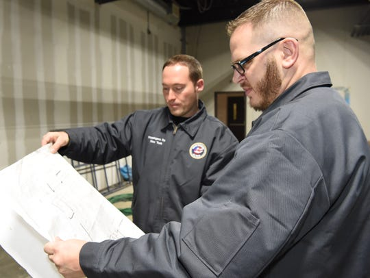 Aaron Browne, right, chief brewer, and Chris Dorn, left, co-owner, look at blueprints for their upcoming business Cousins Ale Works in Wappingers Falls.
