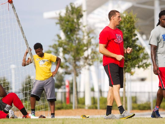 Buffalo Bills wide receiver Sammy Watkins gets advice from Matt Booth, a speed conditioning coach while doing a workout at the soccer fields at City of Palms Park on Thursday 7/10/2014.  Watkins, a Fort Myers native will be receiving a key to the city in a ceremony on Friday.  On the left is Watkins' cousin Willie Neal,13.