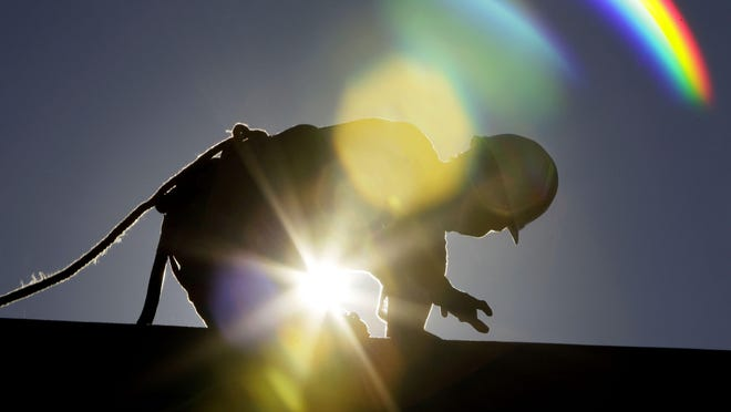 FILE - In this July 6, 2010 file photo, a construction worker is backlit from the morning sun while working on a roof in the heat.