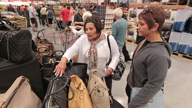 Sally Cardilli and daughter Lisa Cardilli, both of Fairport, look over the selection of handbags at the Costco VIP opening held Thursday night at their new CityGate store on Westfall Avenue in Rochester. The store opens to the public on Friday morning.
