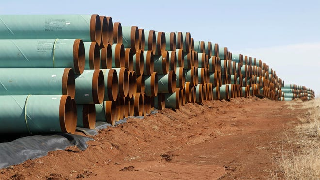 In this 2012 file photo, miles of pipe for the stalled Canada-to-Texas Keystone XL pipeline are stacked in a field near Ripley, Okla.