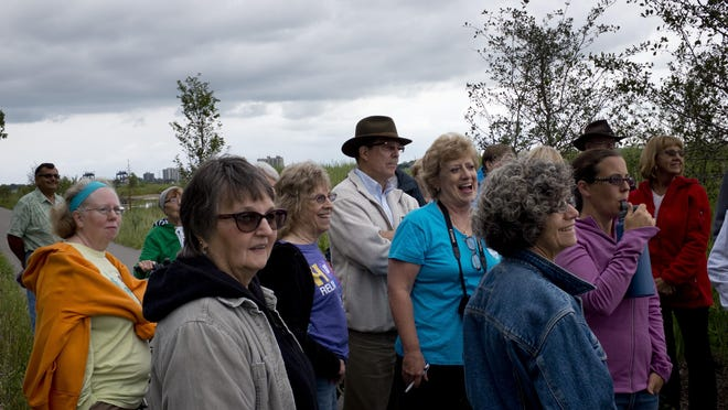 A group of about 25 people listen during a tour Wednesday at the County Wetlands Park on the south end of the Blue Water River Walk in Port Huron.