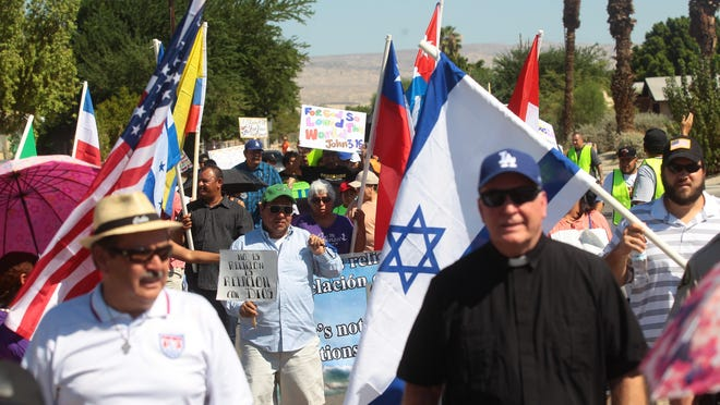 Commuity members participate in a march against violence in Coachella. The event was sponsored by Our Lady of Soledad Catholic Church and Victory Outreach Ministry.