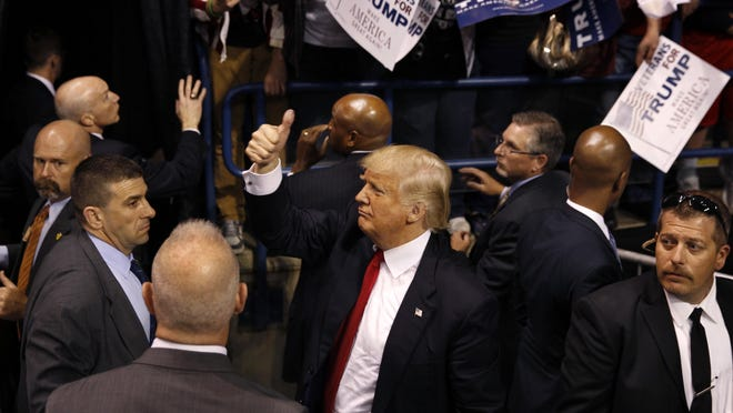 Security stands nearby as Republican presidential candidate, Donald Trump, center, gives a thumbs up to supporters after speaking at a campaign rally Monday, April 25, 2016, in Wilkes-Barre, Pa. (AP Photo/Mel Evans)